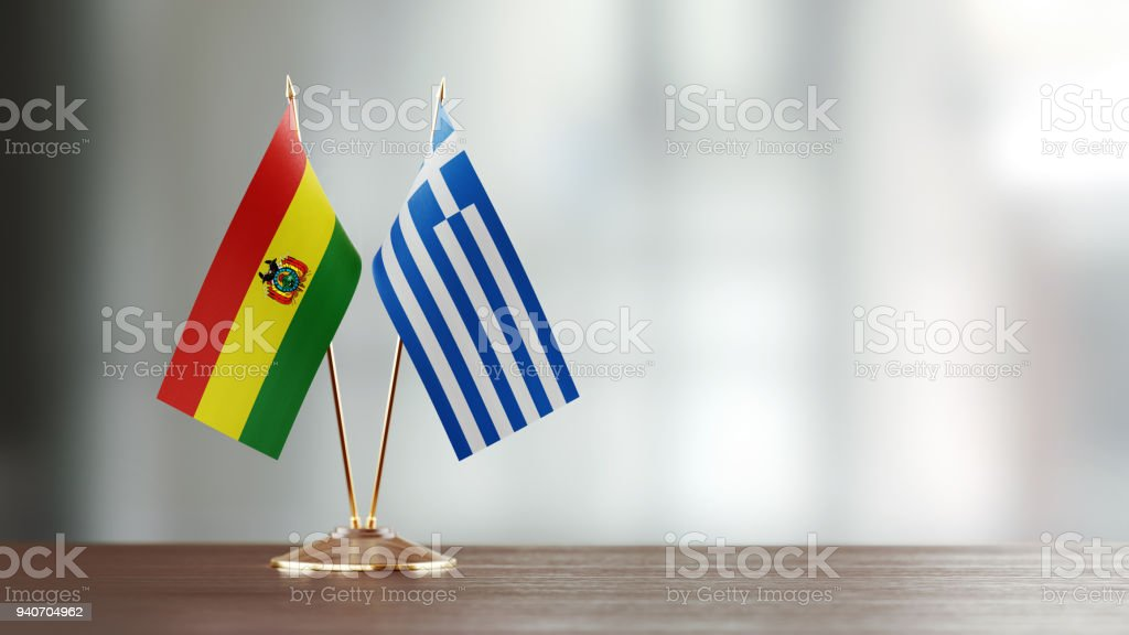 Bolivian And Greek Flag Pair On A Desk Over Defocused Background stock photo