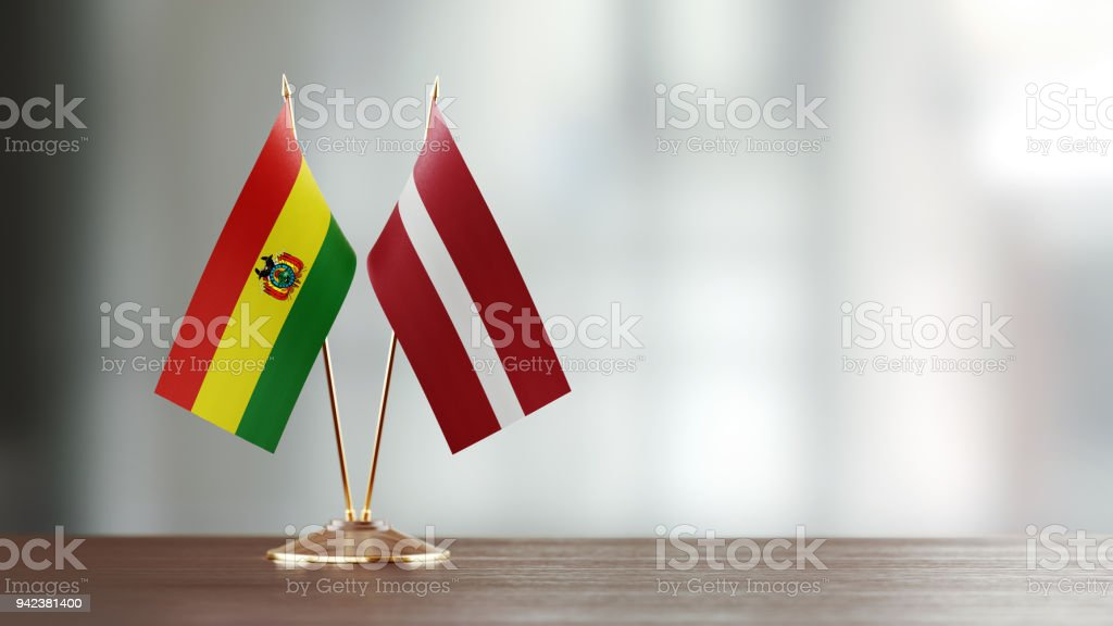 Bolivian And Latvian Flag Pair On A Desk Over Defocused Background stock photo
