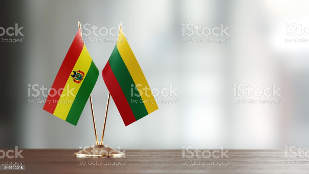 Bolivian And Lithuanian Flag Pair On A Desk Over Defocused Background stock photo