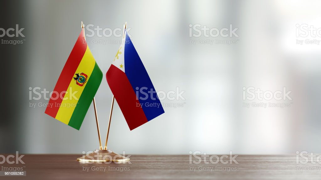 Bolivian And Philippines Flag Pair On A Desk Over Defocused Background stock photo