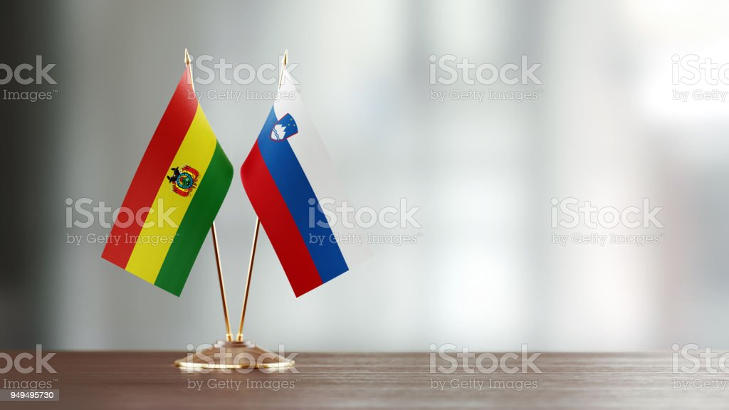 Bolivian And Slovenian Flag Pair On A Desk Over Defocused Background stock photo