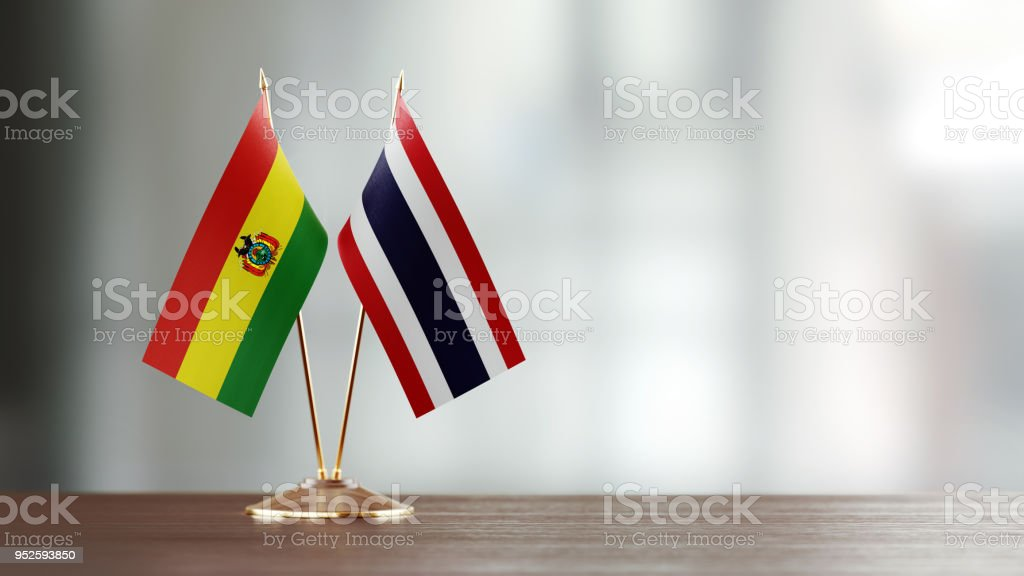 Bolivian And Thai Flag Pair On A Desk Over Defocused Background stock photo