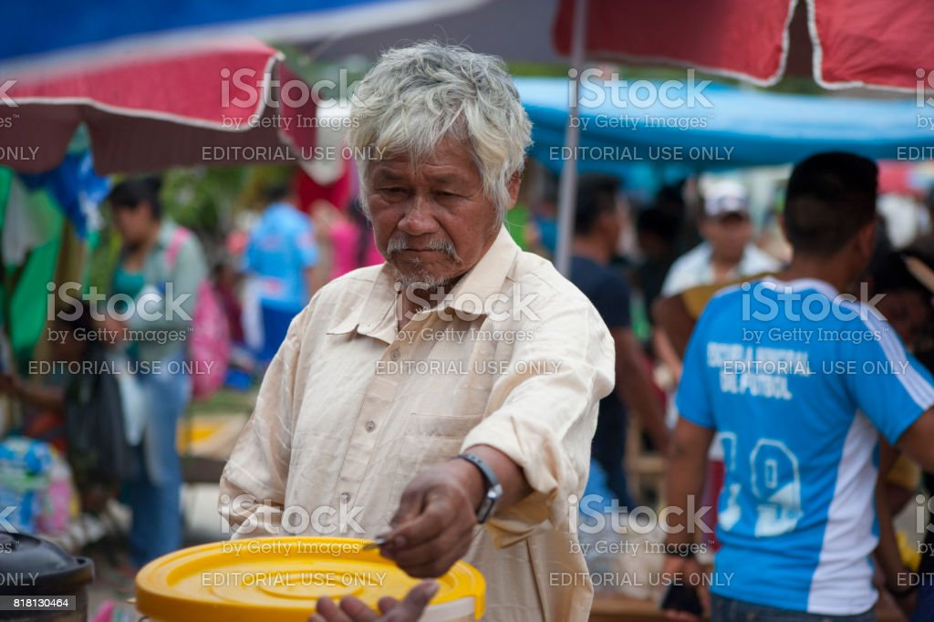 Bolivian old  man paying with a coin in the  Sunday market in Rurrenabaque, Bolivia stock photo