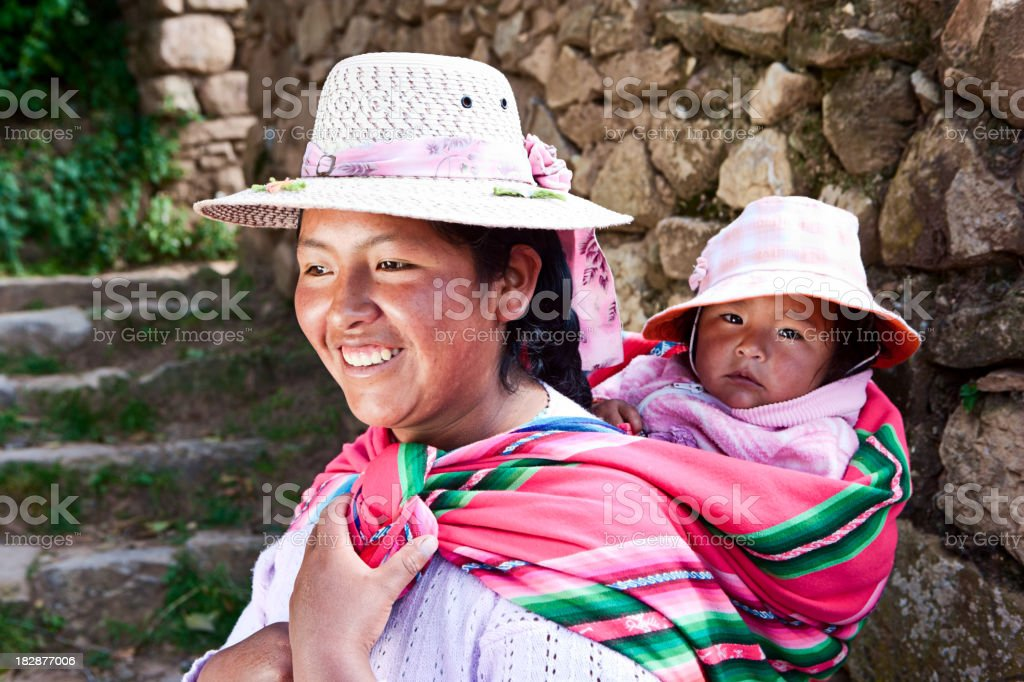 Bolivian woman carrying her baby, Isla del Sol, Bolivia stock photo