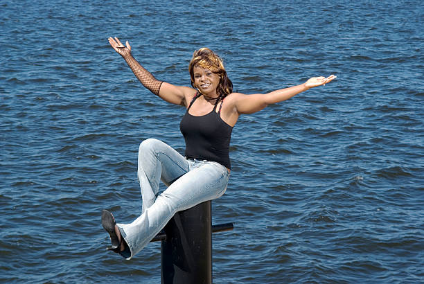 """Bollard I """"Young woman sitting on bollard with arms out, Muskegon, Michigan"""" spaghetti straps stock pictures, royalty-free photos & images"""