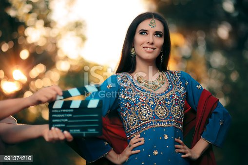 istock Bollywood Actress Wearing an Indian Outfit with Gold Jewelry Set 691374216