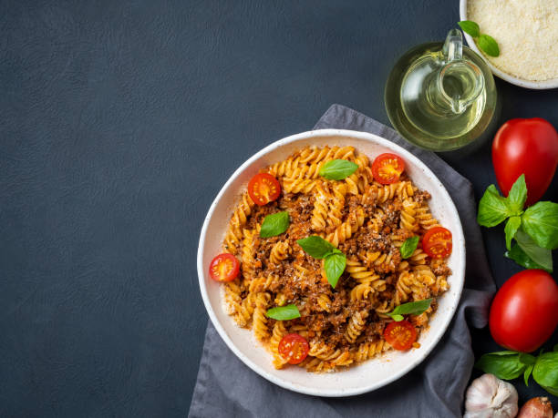 Bolognese pasta. Fusilli with tomato sauce, ground minced beef, basil leaves. Traditional italian cuisine. Top view, copy space. Bolognese pasta. Fusilli with tomato sauce, ground minced beef, basil leaves. Traditional italian cuisine. Top view, copy space fusilli stock pictures, royalty-free photos & images