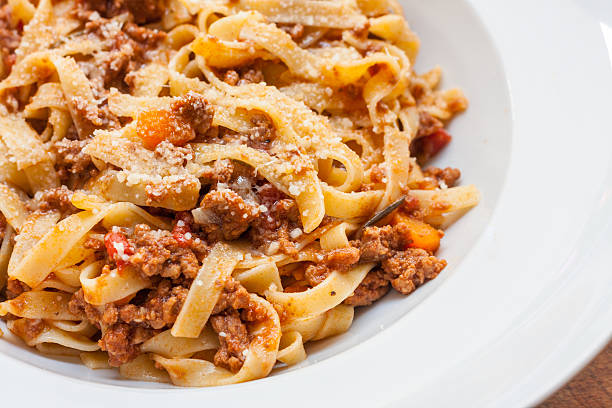 Ragu alla bolognese A classic traditional Italian dish, ragu all bolognese, with tagliatelle in a white bowl tagliatelle stock pictures, royalty-free photos & images