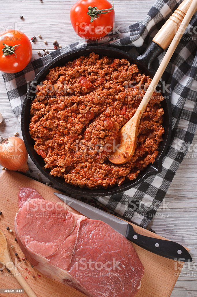 Bolognese sauce in skillet with ingredients vertical top view stock photo
