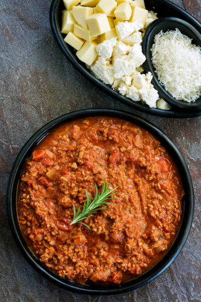 Bolognese Sauce with Italian Cheeses Top View on Slate stock photo