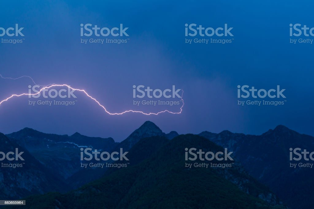 Bolzen-Blitz über Peak Bergsilhouette mit dunkelblauen Himmel – Foto