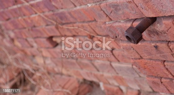 Bokeh view of brick wall, with focus centered on large rusty bolt