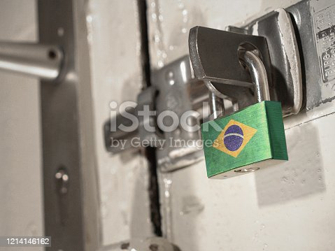 A bolted door secured by a padlock with the national flag of Brazil on it.(series)