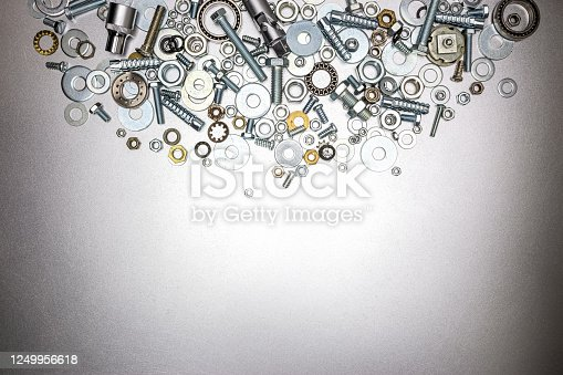 bolts and nuts of different sizes on a grey metallic background. top view