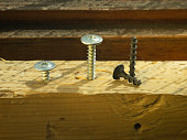 the bolts and screws on a wooden work bench concept of DIY and new screws or bolt .working tools in carpentry and home DIY and self-tapping steel screws