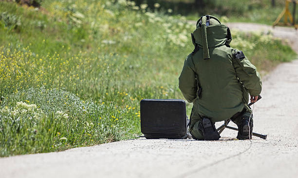 Bomb Disposal EOD Technician in bomb suit setting up a disrupter against a suspected bag on a roadside. explosive stock pictures, royalty-free photos & images