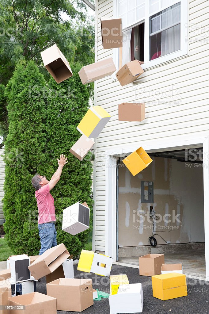 Bombarded by boxes on moving day stock photo