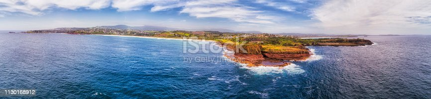 Landscape of elevated coast in Australia along Pacific Ocean around Kiama Bombo Quarry with hexagonal balast pinnacles - wide panorama seen from open sea.