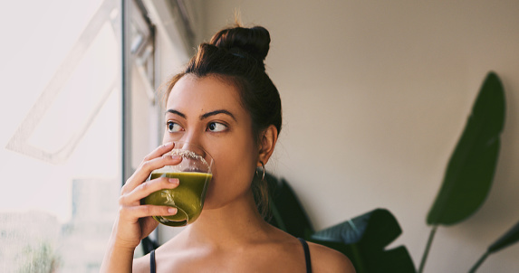 Shot of a young woman drinking a green juice at home