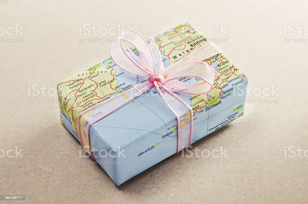 A bon voyage gift wrapped with map paper and pink bow stock photo