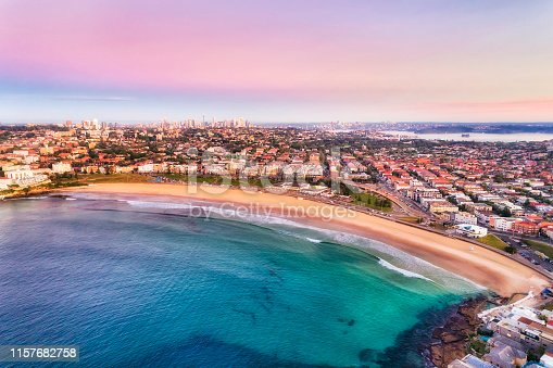 Clean arc of wide sandy Bondi Beach in Sydney at sunrise with pink sky and calm smooth waves floating surfers and surrounded by Eastern suburbs.