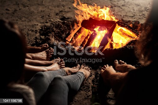 Cropped shot of a group of unrecognizable friends sitting around a bonfire on the beach at night