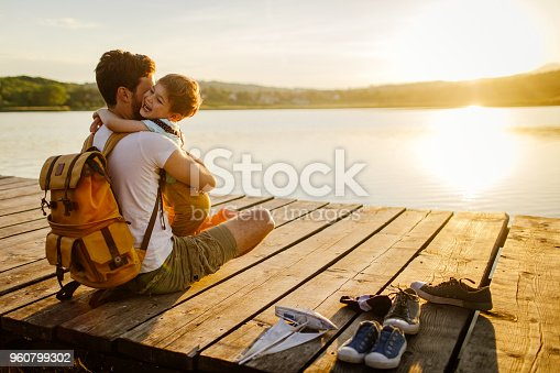 Photo of a young man and his son spending some quality time together while sitting on a lake dock