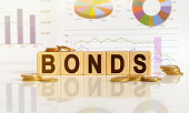 istock Bonds the word on wooden cubes, cubes stand on a reflective surface, in the background is a business diagram. 1255522240