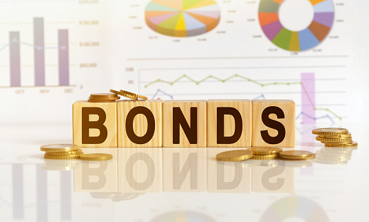 Bonds the word on wooden cubes, cubes stand on a reflective surface, in the background is a business diagram. Business and finance concept
