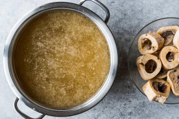 bone broth bouillon in metal pan. - osso foto e immagini stock
