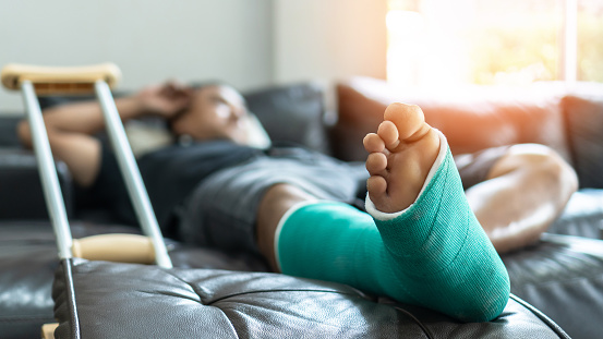 istock Bone fracture foot and leg on male patient with splint cast and crutches during surgery rehabilitation and orthopaedic recovery staying at home 1159293076