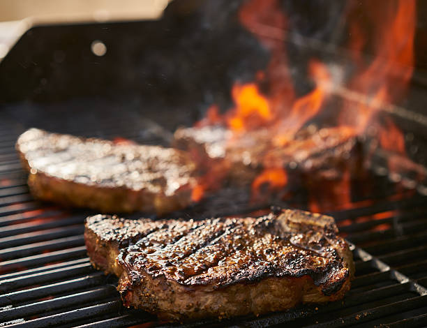 bone-in new york strip steaks cooking over flaming grill stock photo