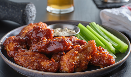 boneless chicken wings covered in honey garlic bbq sauce with ranch and celery on table top