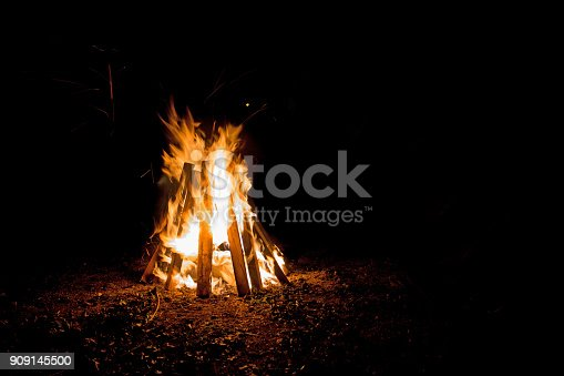 An outdoor bonfire with tall flames contained in boards shaped like a teepee