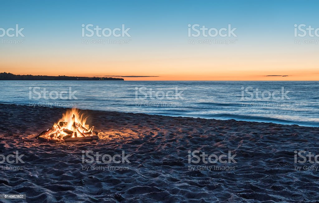 Bonfire at the Beach at Sunset stock photo