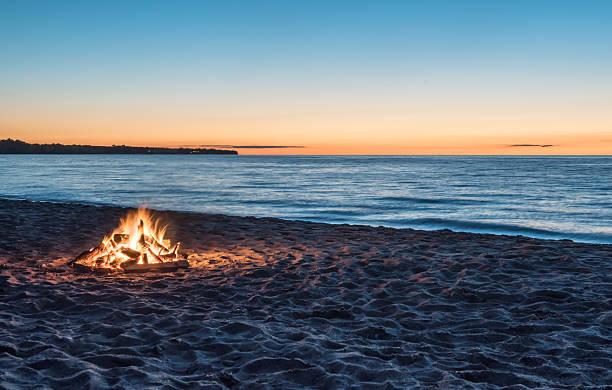 bonfire at the beach at sunset - falò foto e immagini stock