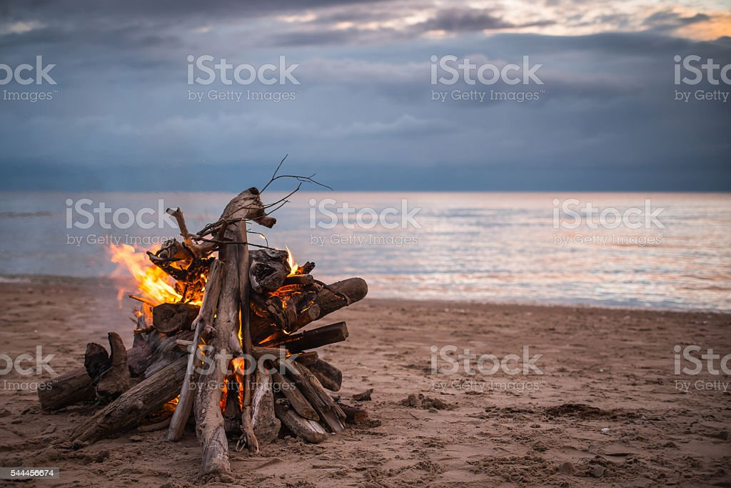 Bonfire at the beach with dramatic clouds圖像檔