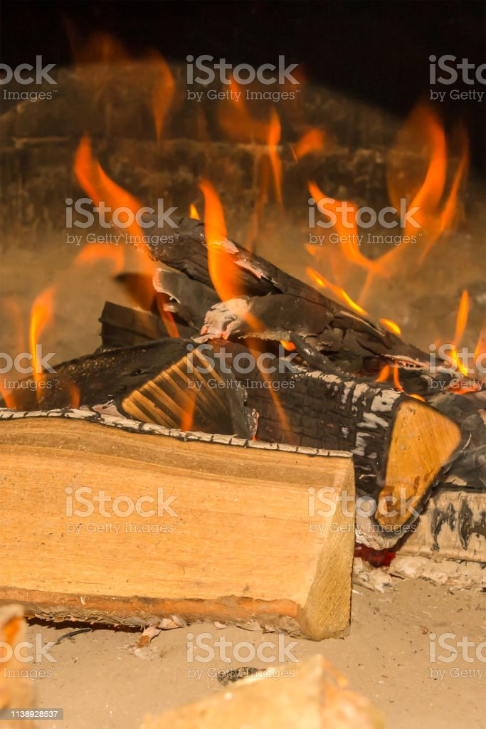 bonfire brightly orange flame large logs burned covered with ash on...