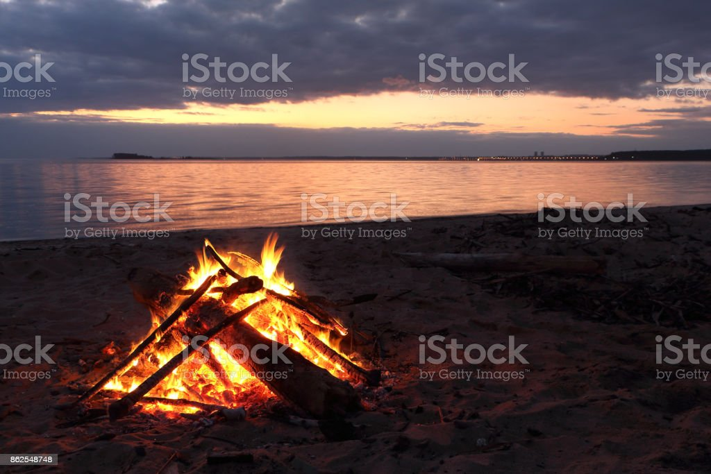 Bonfire burning on the riverbank  on the sunset stock photo