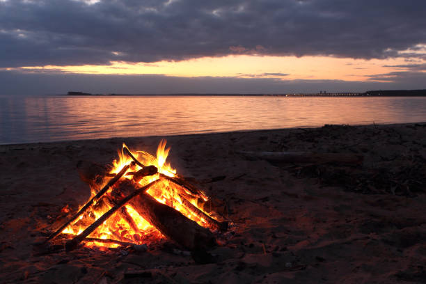 bonfire burning on the riverbank  on the sunset - falò spiaggia foto e immagini stock