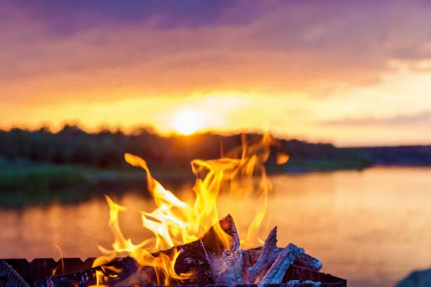 bonfire by the river at sunset - falò spiaggia foto e immagini stock