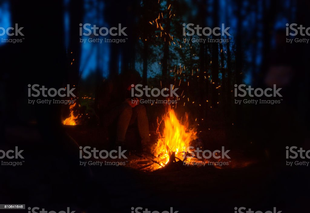 Bonfire in the woods at night, tourist on camping stock photo