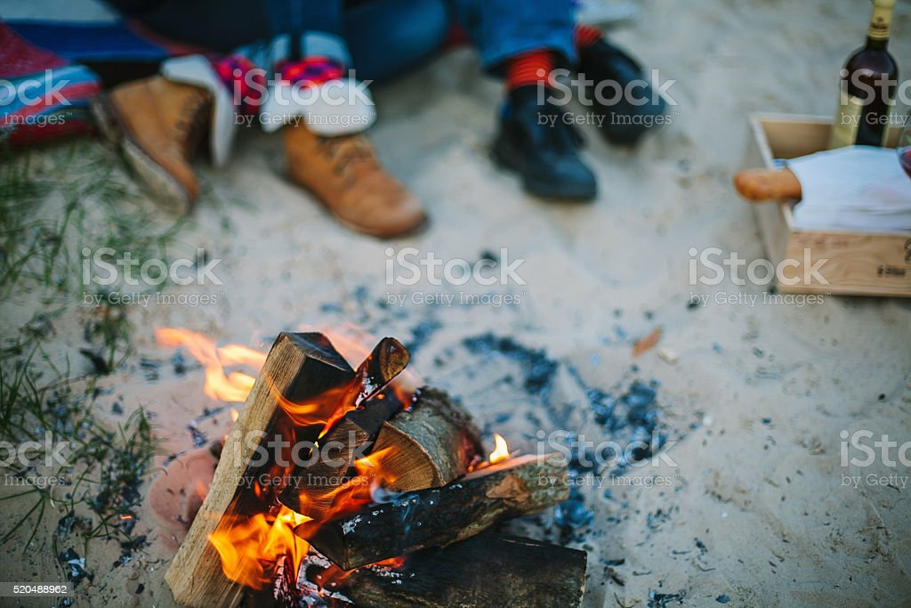 Bonfire on beach and couple on background out of focus.圖像檔