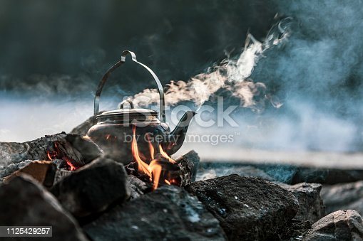 A close-up of a kettle boiling on a fire. There's smoke coming out from the kettle as well as from the fire.