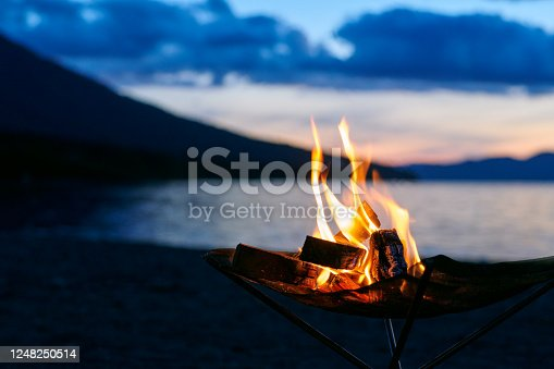 Bonfire time beginning at dusk at lakeside camp