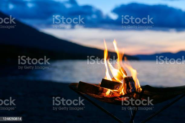 Photo of Bonfire time beginning at dusk at lakeside camp