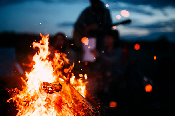 bonfire with sparks flying around - camping stock photos and pictures