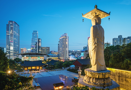 Famous Bongeunsa Temple Buddha Statue at Night, Twilight. Modern Skyscrapers of downtown Seoul illuminated in the background. Seoul, South Korea, Asia.