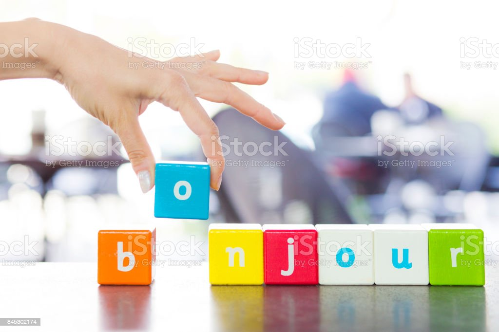 Bonjour, word and hand stock photo