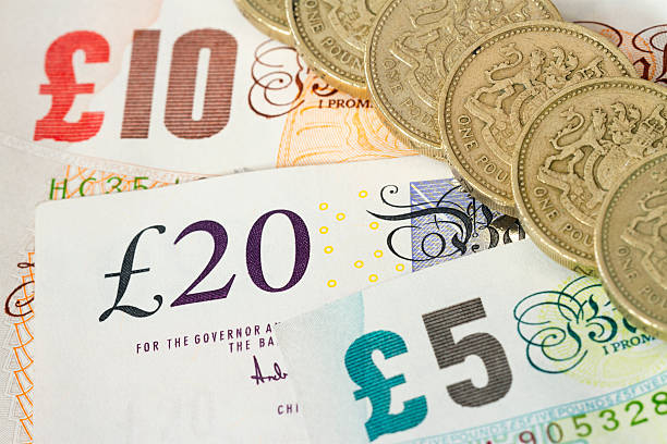 UK Bonknotes y monedas de una libra - foto de stock